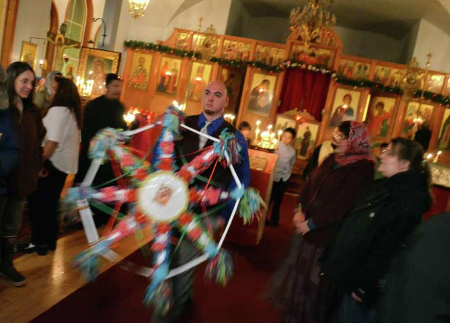 In this photo taken Saturday, Jan. 7, 2012, Kenneth Michener carries the Christmas star out of Kodiak, Alaska's Holy Resurrection Orthodox Cathedral. Saturday was Orthodox Christmas, and in Alaskan tradition, the star leads carolers from home to home. Singers and those carrying the star are welcomed with food and small gifts. Photo: James Brooks, Associated Press / Kodiak Daily Mirror