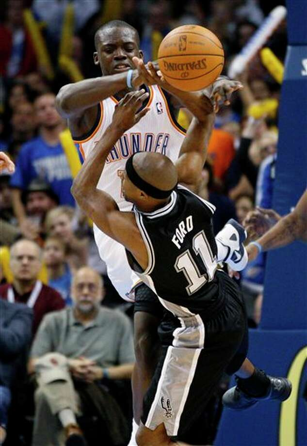 Oklahoma City Thunder guard Reggie Jackson, rear, fouls San Antonio Spurs guard T.J. Ford (11) in the third quarter of an NBA basketball game in Oklahoma City, Sunday, Jan. 8, 2012. Oklahoma City won 108-96. (AP Photo/Sue Ogrocki) Photo: Sue Ogrocki, Associated Press / AP