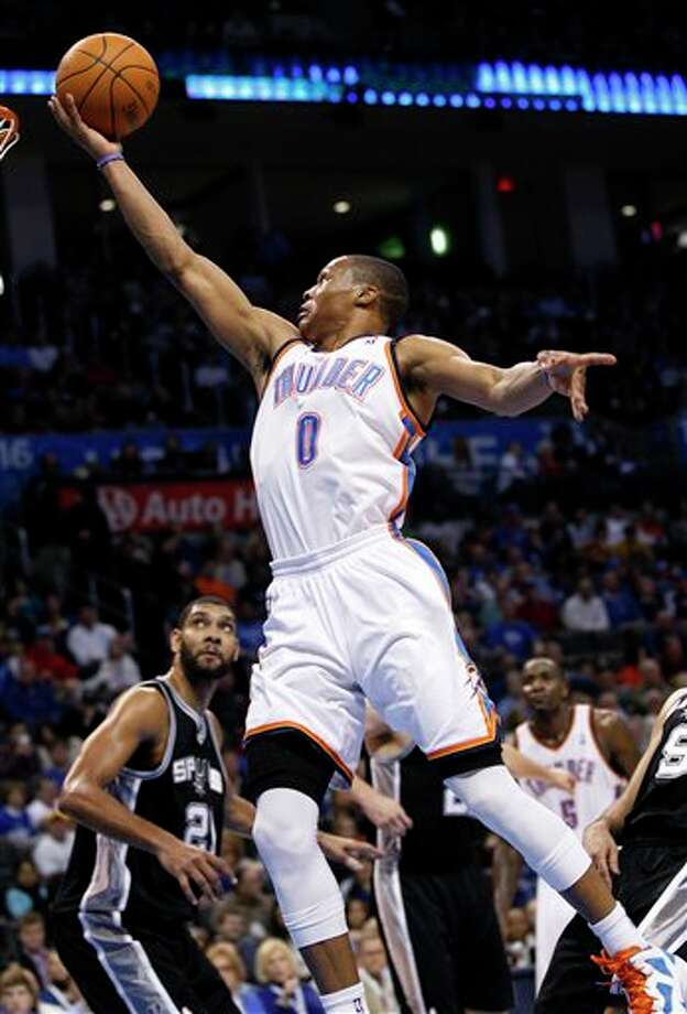 Oklahoma City Thunder guard Russell Westbrook (0) shoots in front of San Antonio Spurs forward Tim Duncan (21) in the third quarter of an NBA basketball game in Oklahoma City, Sunday, Jan. 8, 2012. Oklahoma City won 108-96. (AP Photo/Sue Ogrocki) Photo: Sue Ogrocki, Associated Press / AP