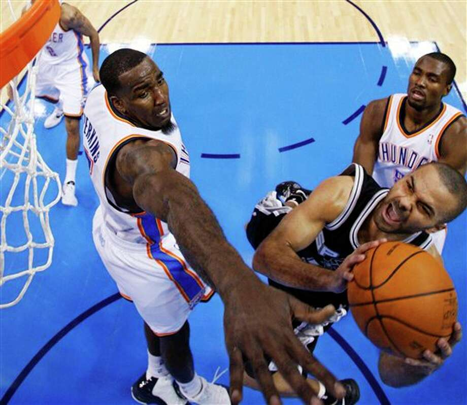 San Antonio Spurs guard Tony Parker, center, shoots between Oklahoma City Thunder center Kendrick Perkins, left, and forward Serge Ibaka, right, in the second quarter of an NBA basketball game in Oklahoma City, Sunday, Jan. 8, 2012. Oklahoma City won 108-96. (AP Photo/Sue Ogrocki) Photo: Sue Ogrocki, Associated Press / AP