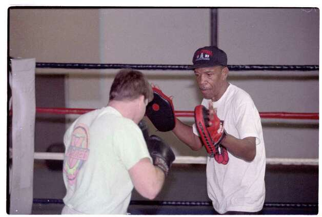 Timothy Goodall Jr., trains boxer Tim Curtis at Main Street Gym in 1994. The Beaumont native spent more than four decades as a trainer. Photo: Timothy Goodall Jr / HC