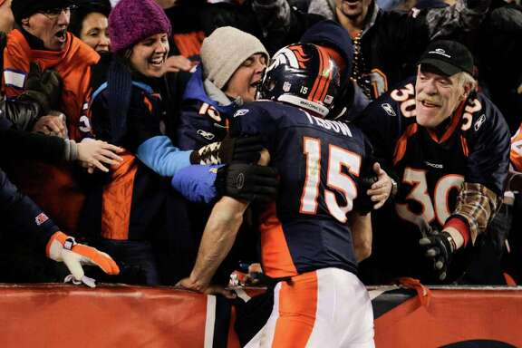 Denver Broncos quarterback Tim Tebow (15) celebrates with fans after wide receiver Demaryius Thomas (88) caught a pass for an 80-yard touchdown to win the game against the Pittsburgh Steelers in overtime of an NFL wild card playoff football game Sunday, Jan. 8, 2012, in Denver.  (AP Photo/Joe Mahoney)