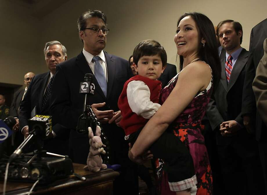 "Sheriff Ross Mirkarimi, with his wife Eliana Lopez and their son Theo by his side,answers question after he was sworn in,  Sunday January 8, 2012, in San Francisco, Calif. When ask about the investigation of domestic violence involving his wife, both she and he replied, "" this is a personal issue."" Photo: Lacy Atkins, The Chronicle"