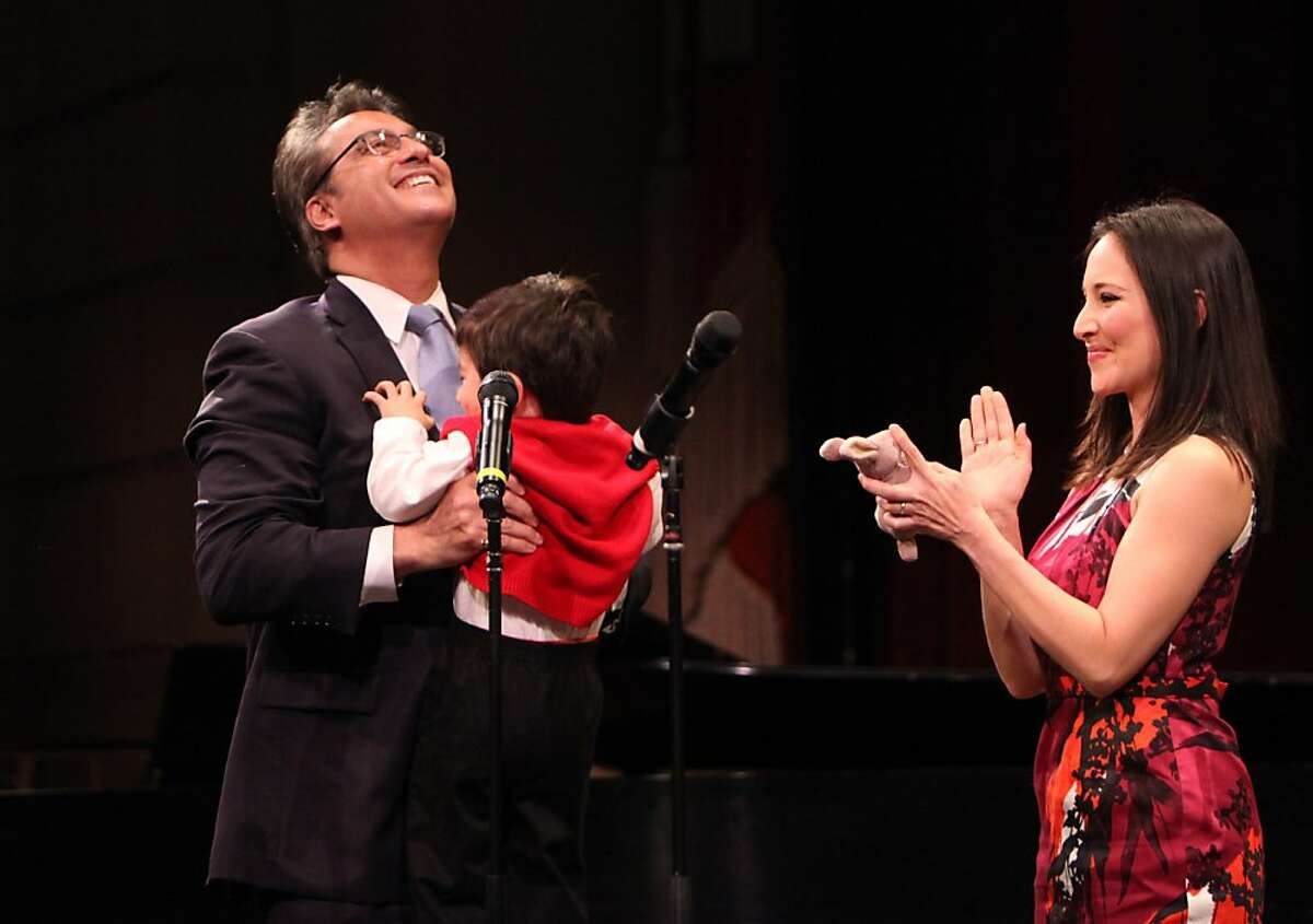 """Sheriff Ross Mirkarimi, lifts his son Theo with his wife Eliana Lopez at his side after being sworn, Sunday January 8, 2012, in San Francisco, Calif. When ask about the investigation of domestic violence involving his wife, both she and he replied, """" this is a personal issue."""""""