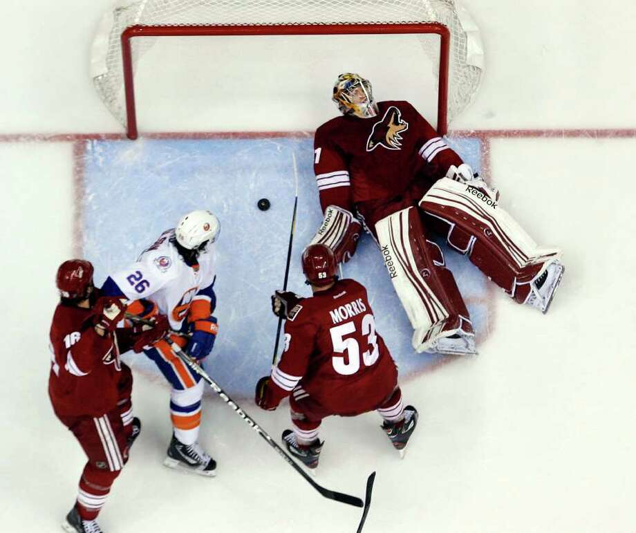 Phoenix Coyotes goalie Mike Smith, right, lies on his back whiletrying to smother the puck as teammates Rostislav Klesla (16) and Derek Morris (53) try to clear out New York Islanders' Matt Moulson  during the second period of an NHL hockey game  on Saturday, Jan. 7, 2012, in Glendale, Ariz. (AP Photo/The Arizona Republic, Emmanuel Lozano )  MARICOPA COUNTY OUT; NO SALES Photo: Emmanuel Lozano