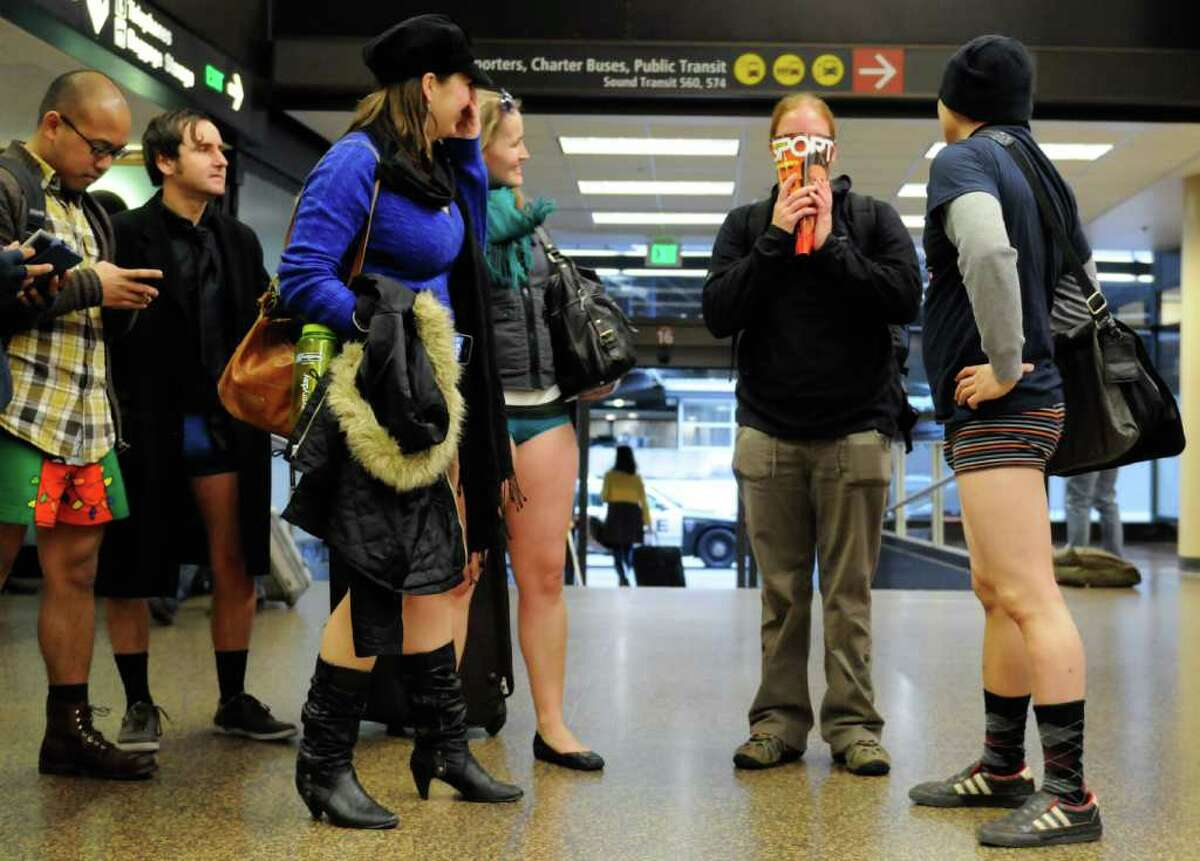 Friends reunite with Heather Ryan, who is hiding her face with a magazine after seeing her friends pantless. She happened to be returning home from Austraiia while her friends participated in the No Pants! Light Rail ride at Sea-Tac Airport.