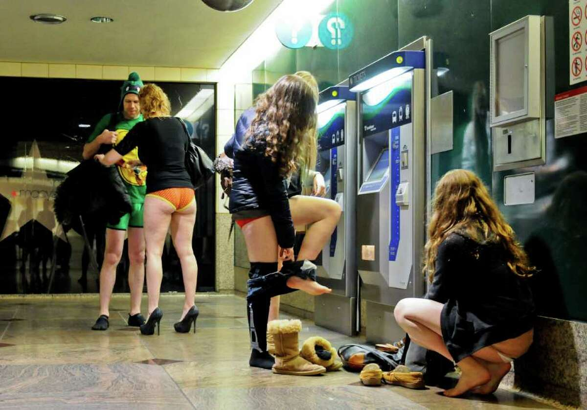 Participants take their pants off while they buy light rail tickets at the Westlake station in downtown Seattle on Jan. 8, 2012. Emerald City Improv hosted the 3rd Annual No Pants! Light Rail Ride as a public performance. Participants met at Westlake Park in downtown Seattle and traveled to Sea-Tac airport via light rail, surprising unsuspecting commuters along the way.
