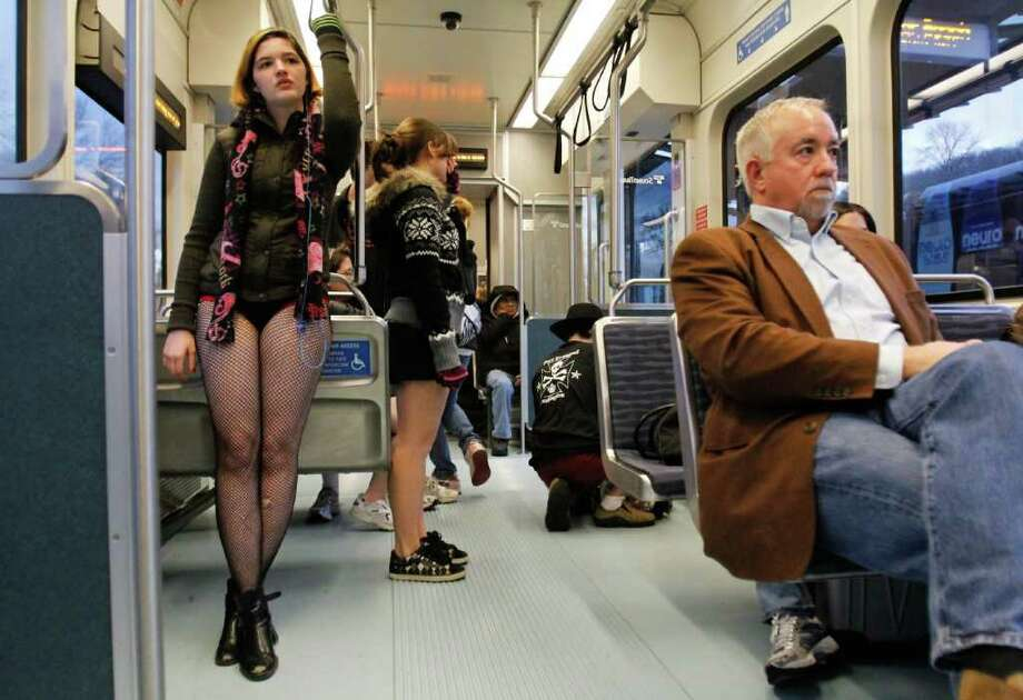 Participant Reshelle Tusing, at left, rides the light rail to Sea-Tac Airport without her pants on Jan. 8, 2012. Emerald City Improv hosted the 3rd Annual No Pants! Light Rail Ride in Seattle on Jan. 8, 2012. Participants met at Westlake Park in downtown Seattle and traveled to Sea-Tac airport via  light rail, surprising unsuspecting commuters along the way. Photo: LINDSEY WASSON / SEATTLEPI.COM