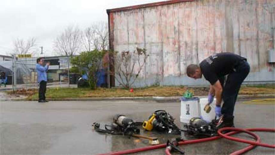 Fire crews collect equipment after the blaze on Heiser. (Cody Duty/Chronicle)
