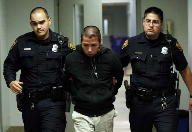 METRO -- Yu Masaki, 27, is escorted out of the San Antonio Police Department headquarters after his arrest, Monday, Jan. 9, 2012. Masaki is suspected in the shooting two Planet Fitness employees Sunday night. A male and female were shot as they were leaving the center. The man died at the scene and the woman was transported to an area hospital. JERRY LARA/glara@express-news.net Photo: JERRY LARA, San Antonio Express-News / SAN ANTONIO EXPRESS-NEWS