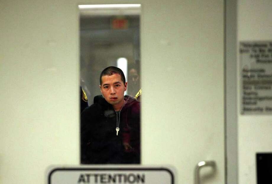 Yu Masaki, 27, is escorted out of the San Antonio Police Department headquarters after his arrest, Monday, Jan. 9, 2012. Masaki is suspected in the shooting two Planet Fitness employees Sunday night. A male and female were shot as they were leaving the center. The man died at the scene and the woman was transported to an area hospital.  Photo: JERRY LARA, San Antonio Express-News / SAN ANTONIO EXPRESS-NEWS