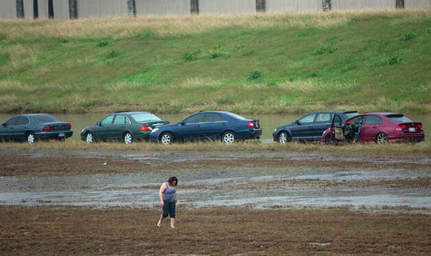 A motorist walks through the median after she was stranded in the Southbound lane of Loop 288 north of the I-610 exit Monday, Jan. 9, 2012, in Houston. (Cody Duty / Houston Chronicle) Photo: HC