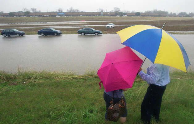 Stranded motorists who wish not to give their names talk beside the Southbound lane of Loop 288 north of the I-610 exit Monday, Jan. 9, 2012, in Houston. (Cody Duty / Houston Chronicle) Photo: HC