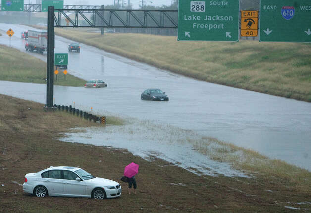 A motorist makes her way to the service road after she was stranded in the Southbound lane of Loop 288 north of the I-610 exit Monday, Jan. 9, 2012, in Houston. (Cody Duty / Houston Chronicle) Photo: HC