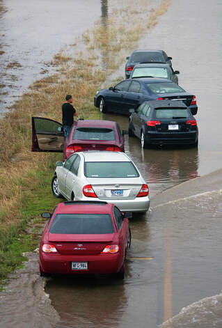A stranded motorist sits in the median of the Southbound lane of Loop 288 north of the I-610 exit Monday, Jan. 9, 2012, in Houston. (Cody Duty / Houston Chronicle) Photo: HC