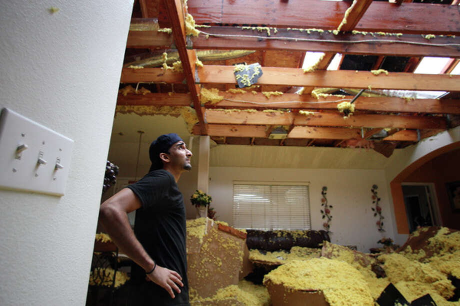 Umair Sayyed looks over damage by a possible tornado inside the home where his he lives with his family in the 15000 block of Turphin Way Monday, Jan. 9, 2012, in Sugar Land. Photo: (James Nielsen / Chronicle)