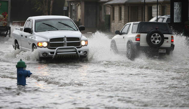 Motorists splash through high water at Alabama and Shepherd after drenching thunderstorms dumped several inches of rain early on Monday, Jan. 9, 2012, in Houston. ( Karen Warren / Houston Chronicle ) Photo: HC