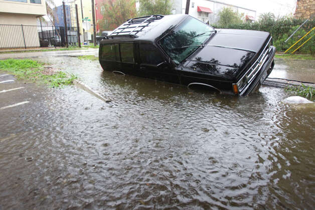 An SUV sits in a flooded ditch during a heavy rain storm Monday, Jan. 9, 2012, in Houston. ( Brett Coomer / Houston Chronicle ) Photo: HC