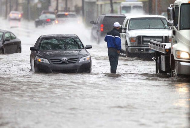 A motorist stands in water near a stalled car on Washington Avenue during a heavy rain storm Monday, Jan. 9, 2012, in Houston. ( Brett Coomer / Houston Chronicle ) Photo: HC
