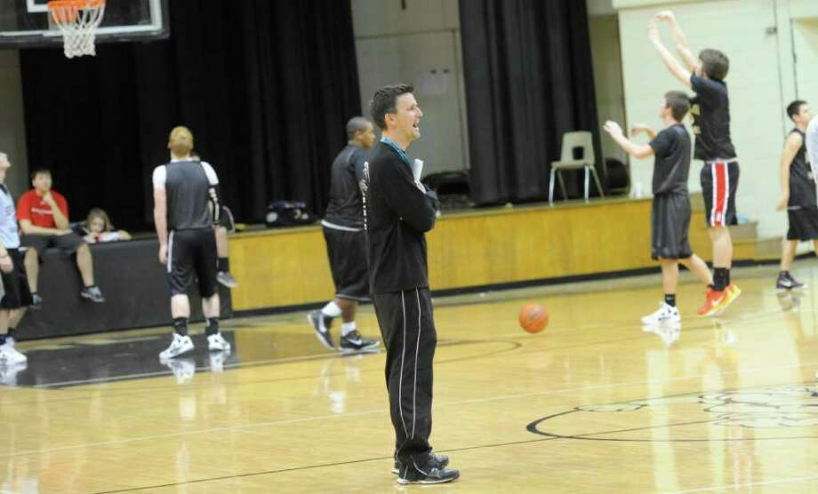 Nederland head boys basketball coach Brian English, center, watches his team start drills Thursday afternoon. The team has continued its success despite losing all five starters from last season. The team was athletic last year and able to pressure teams and get up the floor quickly. Now they rely on their play in the half court. Dave Ryan/The Enterprise