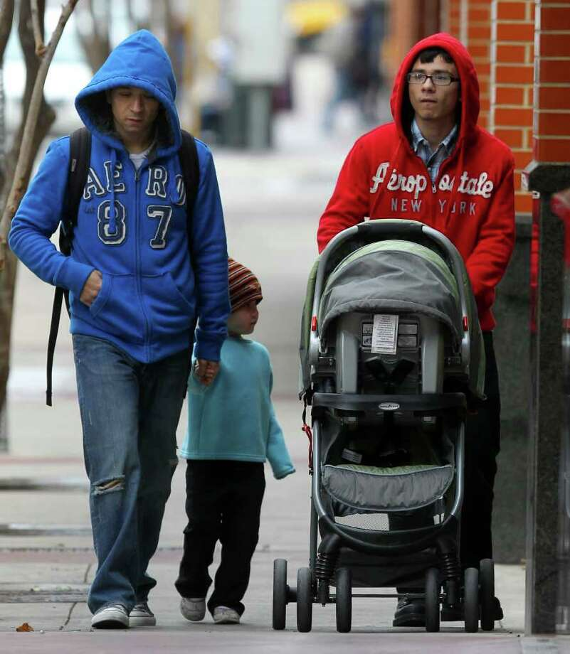 Jon Leija (left) walks in the cold weather with his son Daniel Leija (right) and Lia Leija,4, Monday January 9, 2012 on St. Mary's street in downtown San Antonio. Tuesday's forecast calls for clear skies with temperatures in the low 60s. Photo: JOHN DAVENPORT, SAN ANTONIO EXPRESS-NEWS / SAN ANTONIO EXPRESS-NEWS (Photo may be sold to the public)