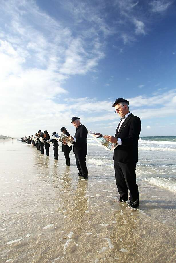 It says here that a tsunami is expected shortly: Volunteers read the morning newspaper while 'waiting for the bus' at Henley Beach in Adelaide, Australia. Surrealist artist Andrew Baines recruited 100 volunteers for this human installation, meant to illustrate corporate workers enjoying nature rather than waiting in a long line for a trip to work. Photo: Morne De Klerk, Getty Images