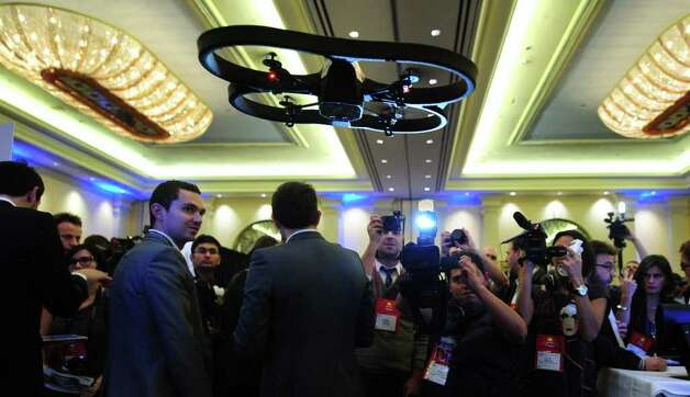 A crowd gathers to watch the Parrot 'A.R.Drone 2.0' flying in mid air during a demonstration at CES Unveiled, ahead of the opening of the annual Consumer Electronics Show on January 8, 2012 in Las Vegas, Nevada. The A.R. Drone 2.0 is the new generation of its reknowned high-tech quadricopter that can be controlled by Wi-Fi using a smartphone or tablet. AFP PHOTO / Frederic J. BROWN Photo: FREDERIC J. BROWN, AFP/Getty Images / 2012 AFP