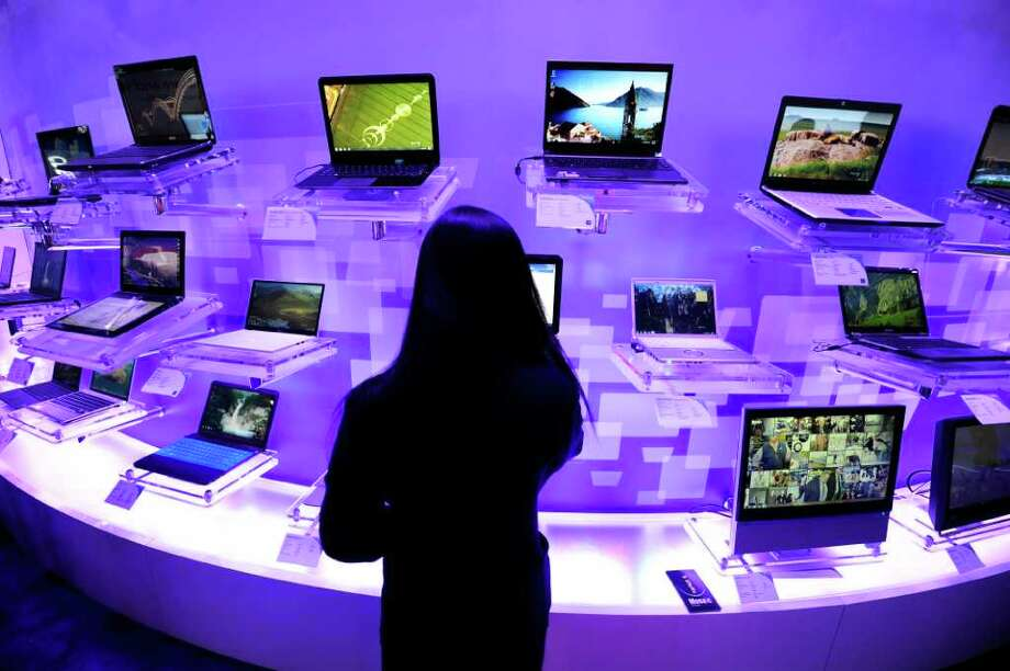 An attendee looks at a laptop computer display at the 2011 International Consumer Electronics Show (CES) January 9, 2011 in Las Vegas, Nevada.   Slick touchscreen tablet computers and smarter devices for the home and the car took center stage as the Consumer Electronics Show (CES) wrapped up here on Sunday.  The always connected lifestyle was on full display at the annual gadget extravaganza as Internet technology ruled at a show traditionally dominated by eye-popping new television sets.  AFP PHOTO  / Robyn Beck Photo: ROBYN BECK, AFP/Getty Images / 2011 AFP