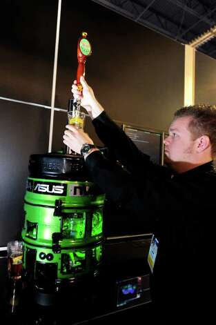 Kris Rey pours beer from a custom-made computer/beer dispenser at the Nvidia booth at the 2011 International Consumer Electronics Show (CES) January 9, 2011 in Las Vegas, Nevada.  The high-powered gaming computer has two Nvidia GeForce GTX 58 video cards in SLI and for a processor the newest Intel i7 Sandy Bridge chip.  It also has a 2.5 gallon (about 40 glasses of beer) beer reservoir with an independent refrigerator system and inline CO2 (carbon dioxide) system for fresh, carbonated, cold beer. The one-of-a-kind computer/beer dispenser will be auctioned for charity.   AFP PHOTO  / Robyn Beck Photo: ROBYN BECK, AFP/Getty Images / 2011 AFP