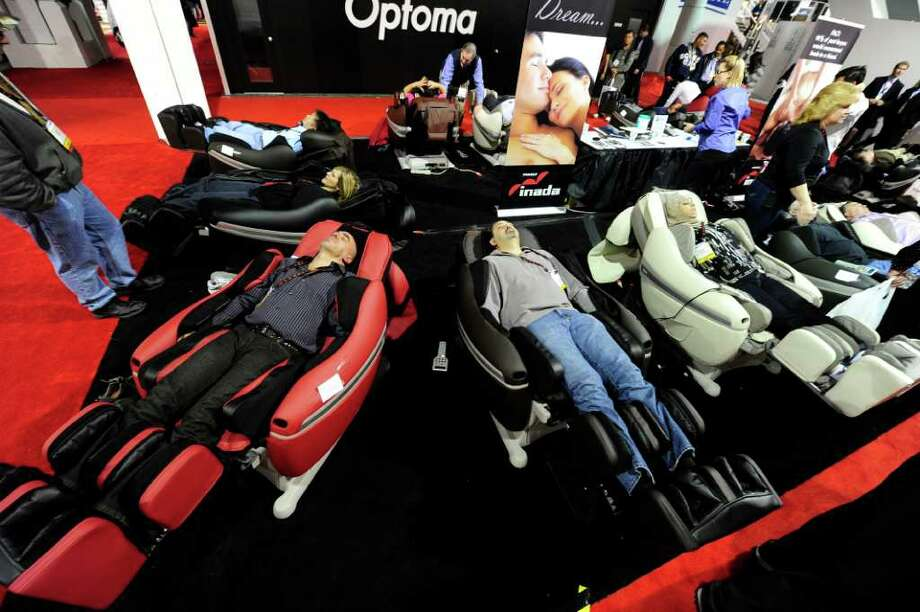 Attendees relaxes in massage chairs at the 2011 International Consumer Electronics Show January 8, 2011 in Las Vega,  Nevada. CES, the world's largest annual consumer technology tradeshow runs through January 9 and is expected to feature 2,700 exhibitors showing off their latest products and services to about 126,000 attendees.     AFP PHOTO / Robyn Beck Photo: ROBYN BECK, AFP/Getty Images / 2011 AFP
