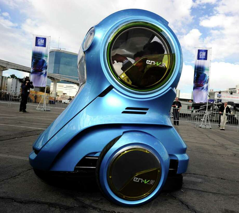 An EN-V Xiao (Smile), an urban mobility concept from GM, on a demonstration drive at the 2011 International Consumer Electronics Show in Las Vegas, Nevada on January 7, 2011.  The EN-V (Electric-Networked Vehicle) is a two-seat electric vehicle designed to address environmental issues and alleviate concerns about traffic congestion, parking availability, energy consumption and affordability for tomorrow's cities.  The EN-V can rotate 360 degrees and be driven in manual mode with a driver or in automous driving mood without a driver in the car.  CES, the world's largest annual consumer technology tradeshow runs from January 6-9.  AFP PHOTO  / Robyn Beck Photo: ROBYN BECK, AFP/Getty Images / 2011 AFP