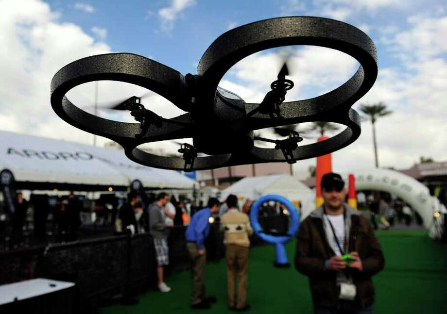 "An attendee (back R) uses a iPhone to control a Parrot AR.Drone at the 2011 International Consumer Electronics Show in Las Vegas, Nevada on January 7, 2011.  The AR Drone is a remote-controlled helicopter equipped with two cameras and controlled over Wi-Fi from an iPhone.  Parrot introduced at CES it's newest AR.Drone dogfighting game, ""Flying Ace"" which features augmented reality machine gun and missiles.  CES, the world's largest annual consumer technology tradeshow runs from January 6-9.  AFP PHOTO  / Robyn Beck Photo: ROBYN BECK, AFP/Getty Images / 2011 AFP"