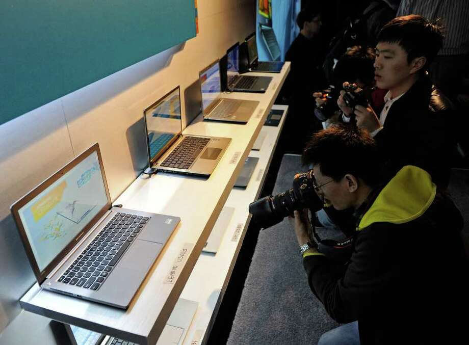 LAS VEGAS, NV - JANUARY 09:  Attendees photograph Ultrabooks displayed during a press event by Intel Corp. at The Venetian for the 2012 International Consumer Electronics Show January 9, 2012 in Las Vegas, Nevada. CES, the world's largest annual consumer technology trade show, runs from January 10-13 and is expected to feature 2,700 exhibitors showing off their latest products and services to about 140,000 attendees. Photo: Ethan Miller, Getty Images / 2012 Getty Images