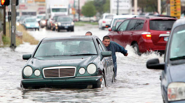 Luis Rodriguez and other friends help a stranded motorist out of high water in the intersection of Fondren and Harwin Drive as a heavy storm continues to move through the Houston area on Monday, Jan. 9, 2012, in Houston. Photo: Mayra Beltran, Houston Chronicle / © 2011 Houston Chronicle