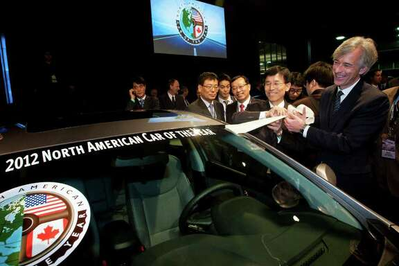 Hyundai Motor America CEO John Krafcik, right, and Hyundai President Seong Hyon Park, second from right, peel off a sticker awarding the 2012 Hyundai Elantra as the North American Car of the Year, at the North American International Auto Show, Monday, Jan. 9, 2012, in Detroit, Mich.