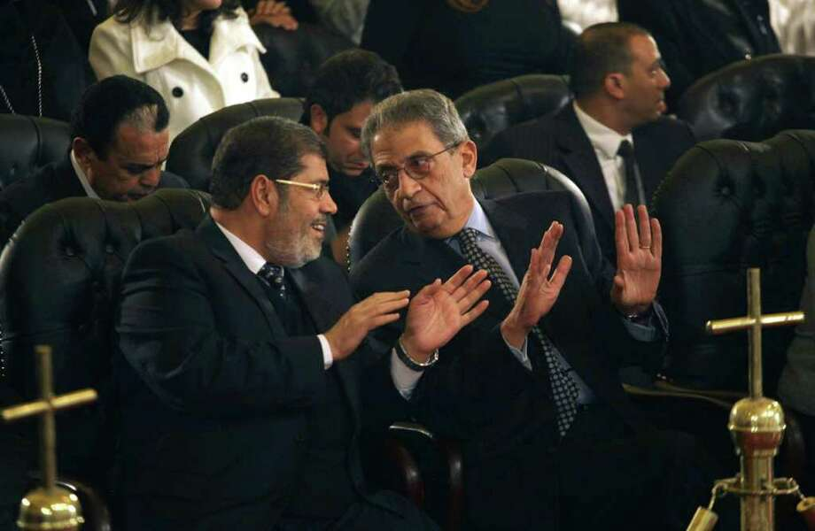 FILE - In this Friday, Jan. 6, 2012 file photo, Mohamed Morsi, left, of Egypt's Muslim Brotherhood and Egyptian presidential hopeful Amr Moussa, right, talk before Christmas Eve mass, led by Coptic Pope Shenouda III at the Coptic cathedral in Cairo, Egypt. The Muslim Brotherhood has emerged as the biggest winner in parliamentary elections, but the fundamentalist group that has long dreamed of ruling Egypt is likely to be cautious about flexing its newfound muscle.(AP Photo/Maya Alleruzzo, File) Photo: Maya Alleruzzo / AP