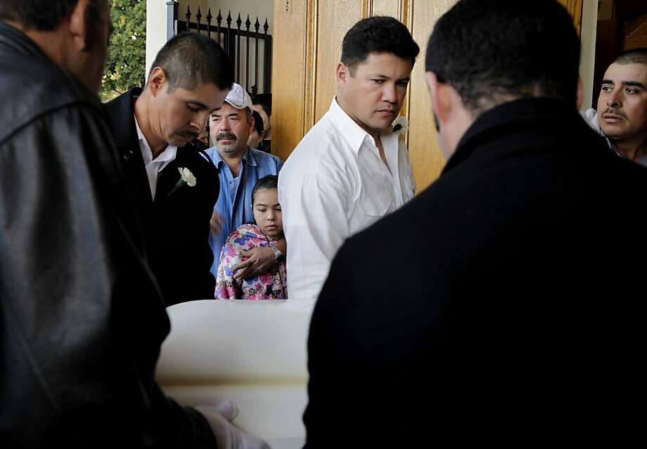 Family members watch as the pallbearers carry the coffin of Gabriel Martinez Jr. into St. Elizabeth Church, Friday January 6, 2012, at the St. Elizabeth Church in Oakland, Calif. Gabriel Martinez Jr., 5-years old was killed December 30 while standing outside his father's taco truck. Photo: Lacy Atkins, The Chronicle