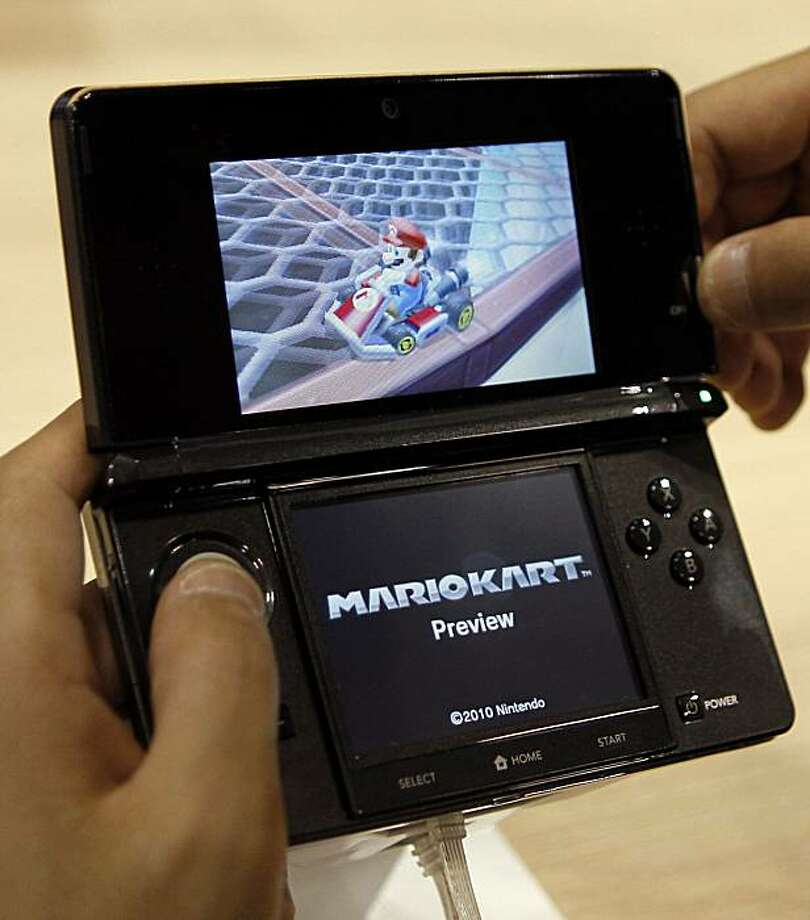 File - In this Sept. 29, 2010 file photo, a visitor operates a Nintendo 3DS featuring 3-D imagery during a press conference by Nintendo Co. President Satoru Iwata where he launches the new game machine which will hit the Japanese market in Feb., 2011 in Chiba near Tokyo, Japan. Nintendo reported Thursday, Oct. 28, 2010, it sank into the red for the fiscal first half, battered by a rising yen that hurts exports and plunging sales as demand for its game machines ran out of steam. Photo: Shuji Kajiyama, AP