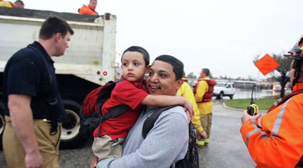 Jose Encinia right and his four-year-old son Jonathan Encinia walk away after Houston Fire Department personnel used a City of Houston dump truck during high water rescues at a school near Griggs Road and Martin Luther King Boulevard Monday, Jan. 9, 2012, in Houston. ( James Nielsen / Chronicle ) Photo: James Nielsen, Houston Chronicle / © 2011 Houston Chronicle