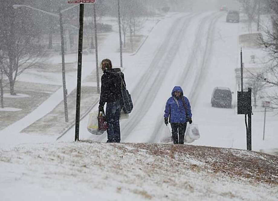 Two women walk up a hill off of S. Irving Street and Iowa Avenue in Denver, Thursday, Dec. 30, 2010. Storm hits the Denver Metro area, late Thursday morning with very cold temperatures that could cause icy streets and overpasses. Photo: John Prieto, AP