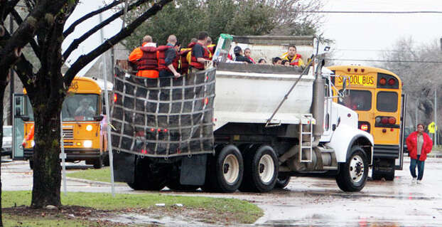 Houston Fire Department personnel use a City of Houston dump truck during high water rescue of a school near Griggs Road and Martin Luther King Boulevard Monday, Jan. 9, 2012, in Houston. ( James Nielsen / Chronicle ) Photo: James Nielsen, Houston Chronicle / © 2011 Houston Chronicle