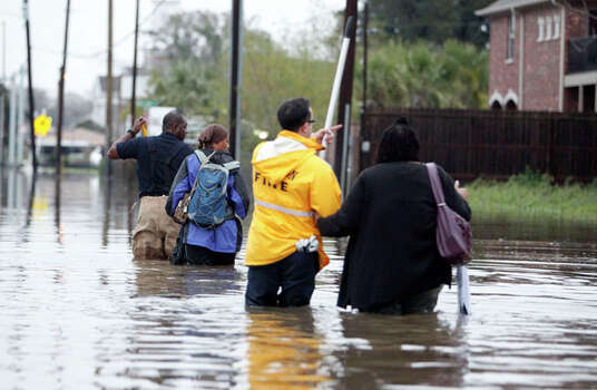 Houston Fire Department firefighters escort Dominga Britton 2nd from left and Denean Flanagan right, to their homes during high water rescues near Griggs Road and Martin Luther King Boulevard Monday, Jan. 9, 2012, in Houston. ( James Nielsen / Chronicle ) Photo: James Nielsen, Houston Chronicle / © 2011 Houston Chronicle