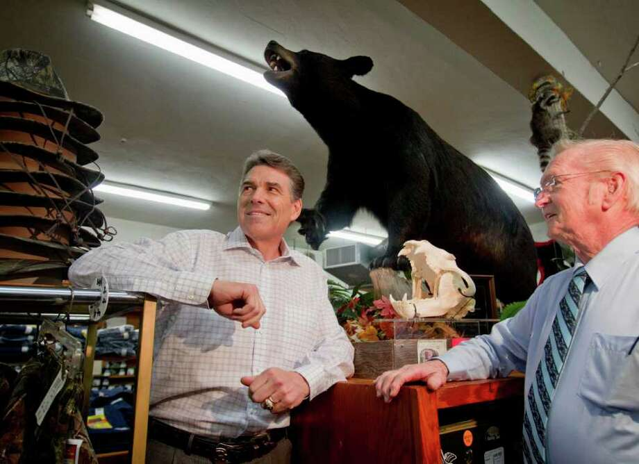 Campaigning in South Carolina on the eve of the New Hampshire vote, Republican presidential candidate Texas Gov. Rick Perry visits with Glenn Brock, owner of Brock's department store, during a stop Monday in Pickens, S.C. Photo: David Goldman / AP