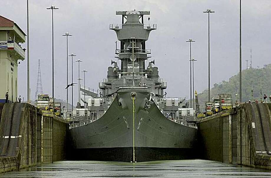 The USS Iowa crosses the Panama Canal at Miraflores Lock near Panama City, Panama Wednesday, March 28, 2001.  At 108.2 feet wide, the Iowa-class battleships are the largest vessels ever to scrape their way through the 110-foot-wide locks of the canal. They were designed so that they could just fit through the waterway. Photo: Tomas Munita, AP