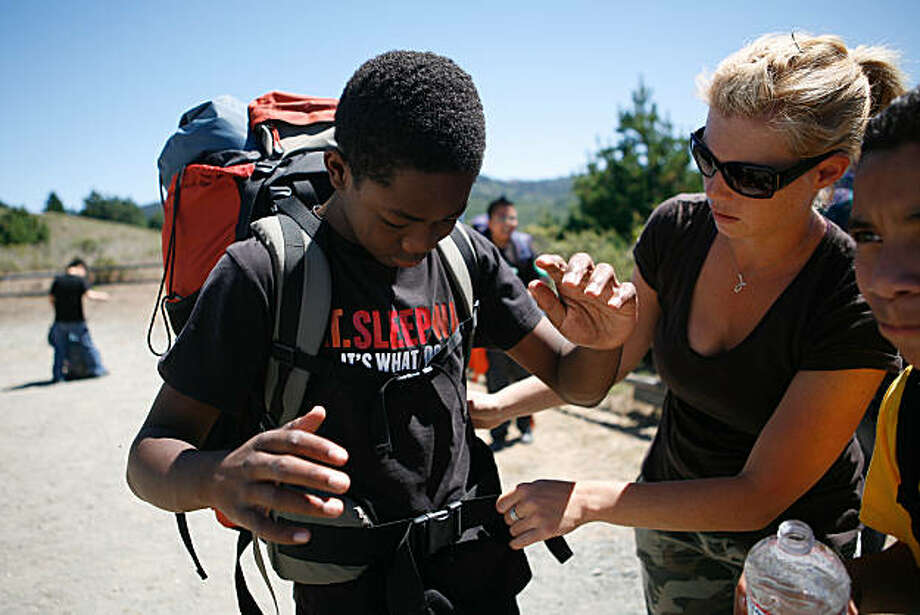 Jill Johnson, a seventh grade math and science teacher at the Urban Promise Academy, helps Jakell Watts, 12, put on a outdoor backpack at the Point Reyes National Seashore in Marin County, Calif. on Wednesday September 1, 2010. Each year the entire seventh grade class of the Urban Promise Academy, a middle school located in the Fruitvale neighborhood of Oakland Calif., goes on a three day trip to the Point Reyes National Seashore where many students go camping and hiking for the first time in their lives. The Urban Promise Academy received outdoor gear, like Jakell's backpack, as well as outdoor training from Bay Area Wilderness Training, an organization headquartered in Oakland, Calif. with the mission of providing at risk urban youth first hand experience in the wilderness. Bay Area Wilderness Training, or BAWT, grants full access to its gear library to those schools and organizations who complete its wilderness training program. Photo: Jasna Hodzic, The Chronicle