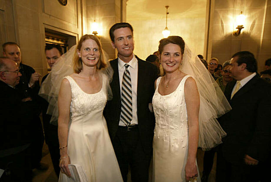 San Francisco Mayor Gavin Newsom stands between newlyweds Cissie Bonini, left, and Lora Pertle, during a reception at San Francisco City Hall in this Friday, Feb. 13, 2004, file photo. Photo: Kim Komenich, The Chronicle
