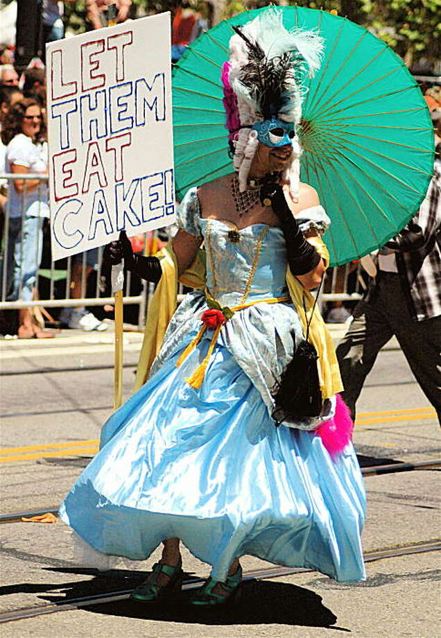 "This reveler channels Marie Antoinette in an old-fashioned dress and elaborate wig, complete with a sign reading ""Let them eat cake!"" Photo: Rsjaeger, Reader Photo"