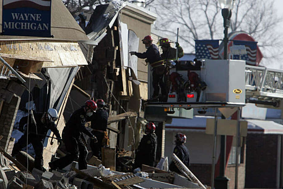 Rescuers comb through the rubble looking for at least two employees believed to be trapped after an explosion at William C. Franks furniture store, Wednesday, December 29, 2010, in Wayne, Michigan. (Andre J. Jackson/Detroit Free Press/MCT) Photo: Andre J. Jackson, MCT