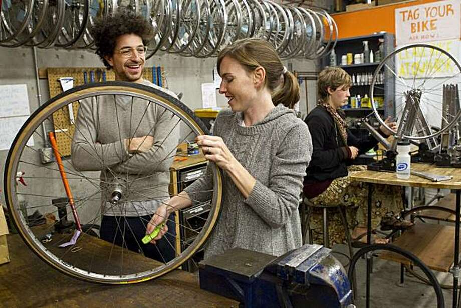 Reporter  Regina Sinsky learns how to replace a tube in her bike tire from Rafi Ajl at The Bike Kitchen in San Francisco, Calif., on Thursday, December 16, 2010. Photo: Laura Morton, Special To The Chronicle
