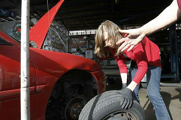Regina Sinsky learns how to change a tire  maintain her car at San Francisco Auto Repair Center on Wednesday, December 15, 2010, San Francisco, Calif.  Sinsky starts the New Year with a resolution to take on more repairs. Photo: Adm Golub, The Chronicle